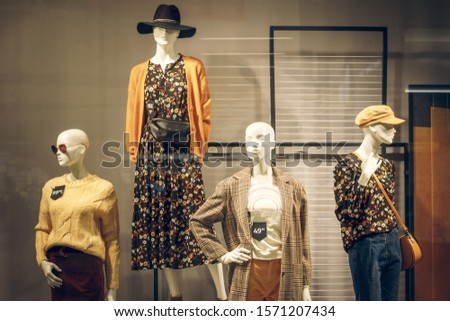 Female mannequins in shop window. Standing women dummies show casual style collection of clothes in showcase