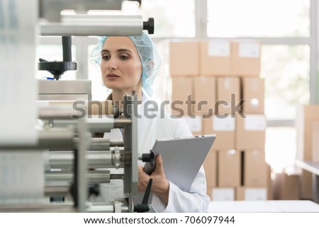 Female manufacturing supervisor looking worried while checking equipment and production during quality control in the interior of a cosmetics factory