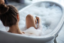 female massaging her legs with sponge in the tub. back view shot