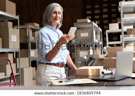 Female mature senior small business owner using mobile app checking parcel box. Older entrepreneur seller holding cell phone tech device preparing retail package postal shipping order in warehouse.