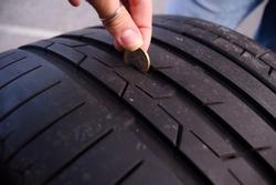 Female Measuring tire depth using a small coin
