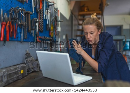 Female Mechanic. Female mechanic with laptop. Young female mechanic with laptop. Business woman at a factory. Craftswoman working using a laptop in the garage