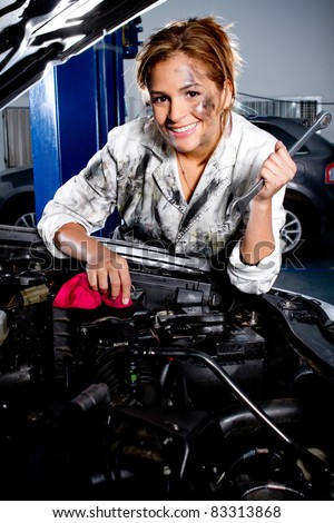 Female mechanic fixing a car at the garage