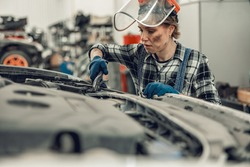 Female mechanic holding a pair of locking pliers in her hand