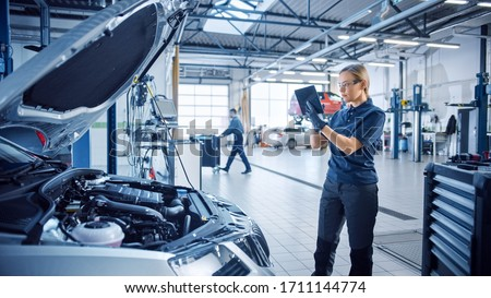 Female Mechanic Uses a Tablet Computer with an Augmented Reality Diagnostics Software. Specialist Inspecting the Car in Order to Find Broken Components Inside the Engine Bay. Modern Car Service. Foto stock ©