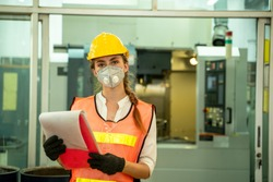 Female Mechanic wearing  protective mask to Protect Against Covid-19,Female technician worker working and checking machine in a large industrial factory,Coronavirus has turned into a global emergency