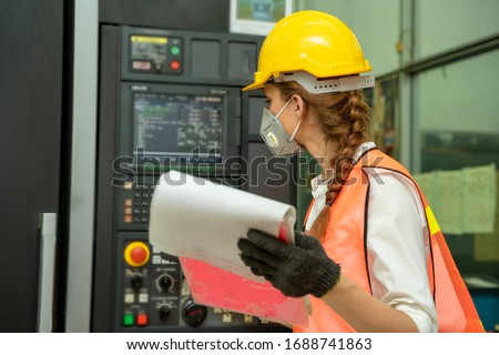 Female Mechanic wearing protective mask to Protect Against Covid-19,Female technician worker working and checking machine in a large industrial factory,Coronavirus Disease 2019 (COVID-19) concept.