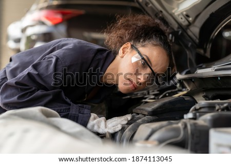 Female mechanic working at the garage. Professional female car mechanic examining, repair and maintenance under hood of car at auto car repair service. Car service and Maintenance concept Photo stock ©