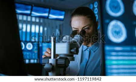 Female Medical Research Scientist Looking Through the Microscope Types Acquired Data in the Computer. Laboratory. In the Laboratory with Multiple Screens Showing MRI / CT Brain Scan Images.