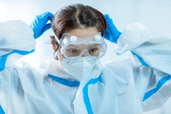 female medical worker wear protective goggles and ready to take care of coronavirus patient in isolation room