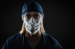 Female Medical Worker Wearing Protective Face Mask and Gear Against Dark Background.