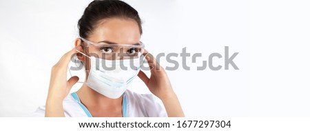 Female Medical Worker Wearing Protective Face Mask, goggles and Gear isolated on white Background. woman Doctor or Nurse Wearing Scrubs, Protective Face Mask and transparent Goggles.