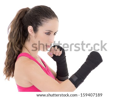 Female mixed martial arts fighter in MMA style gloves strikes a fight stance