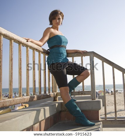 Female model in blue top and black leaning on a railing at the beach #5915623
