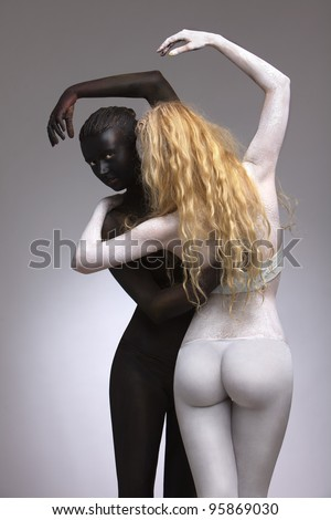 female model painted in white, black colors artistically posing in studio