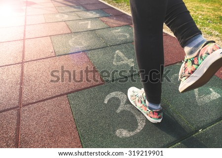 Female model playing hopscotch game outdoor.