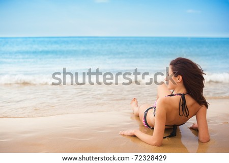 Female Model, Sitting back/Relaxing on Sand, facing sideways to the sea, as waves come in, at the beach.