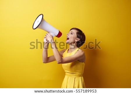 Female model using bullhorn in photo session