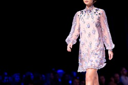 Female model walks the runway in pink dress isolated on a black background during a Fashion Show. Fashion catwalk event showing new collection of clothes. Single female model in beautiful dress.