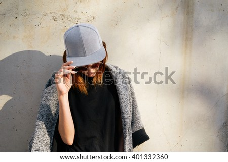 Female model wearing a black blank cap and sunglasses looking away. Portrait of a young beautiful girl with cap