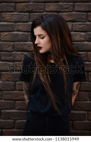 Female model with tattoos, piercing in nose, black lips and long brunette hair. Beautiful slim girl with tattoos wearing black t shirt and jeans standing against the stone wall or brick fence. #1138015949