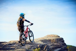 Female MTB mountain biker enjoys the view during cycling trip