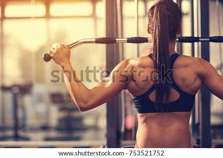 Female muscular bodybuilder exercising #753521752