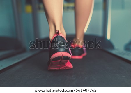 Female muscular feet in sneakers running on the treadmill at the gym. Concept for fitness, exercising and healthy lifestyle.