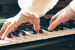 Female musician playing the digital piano or electronic keyboard at home. Music Education and Entertainment. Online music lessons.