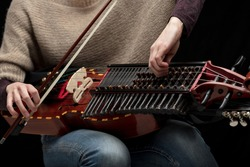 Female musician tuning her modern reconstruction of a medieval Swedish nyckelharpa before a performance in close up on the instrument keys and tangents