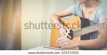 Female musicians play guitar and write songs using the tablet.This image is blurred and soft focus. #676733101