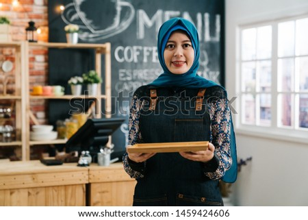 female muslim cafe worker greeting customer in coffee shop. young malay girl in apron holding tray face camera smiling confident in bar in morning. islam lady start up business owner in modern store.