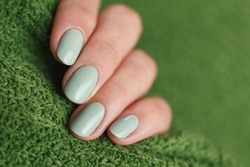 Female neat hand with short natural nails painted with mint nail polish holding knitted green fabrics. Natural, cozy, elegant, modern look.