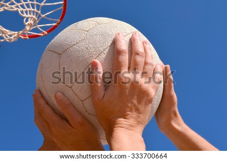 Female netball players struggle for a netball with a netball hoop and ring in the background.