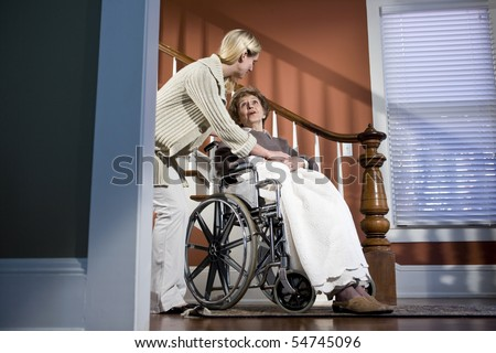 Female nurse helping elderly woman in wheelchair at home