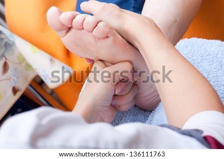 female Nurse massaging foot of a patient, closeup