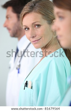Female nurse standing in the middle of two colleagues