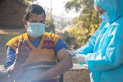 Female Nurse with PPE kit protective mask and gloves preparing a male patient's arm for vaccination in Rural village of India. Healthcare workers giving vaccine to a people in pandemic.