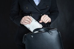 female office worker company steals and hides a hard drive with corporate financial information in a bag to sell to competitors