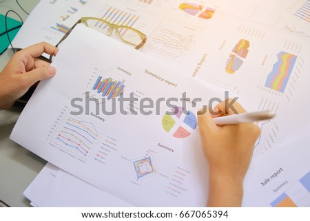 Female office workers holding are arranging documents of unfinished documents archive analyzing the market and considers on the size of future profits on table office. Stack of business paper.  #667065394