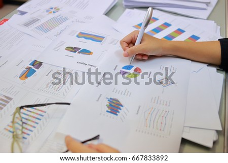 Female office workers holding are arranging documents of unfinished documents archive analyzing the market and considers on the size of future profits on table office. Stack of business paper.  #667833892