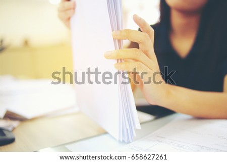 Female office workers holding  are arranging documents of unfinished documents on office desk, Stack of business paper. #658627261