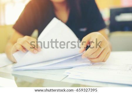 Female office workers holding  are arranging documents of unfinished documents on office desk, Stack of business paper.