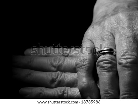 Female old hand with two wedding rings on the finger on horizontal black background.
