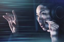 Female operator with headphones touching virtual screen