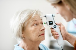 Female ophthalmologist measuring the eye pressure with modern tonometer to a senior patient in the medical office, close-up view