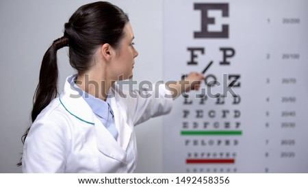 Female ophthalmologist showing letters on eye chart, vision check up, health Foto d'archivio ©