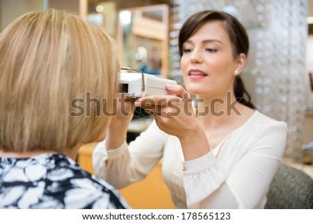 Female optometrist measuring pupilary distance on senior patient