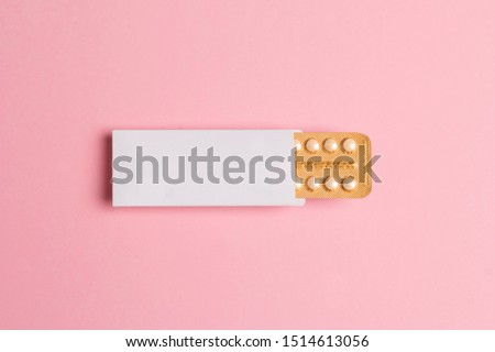 Female oral contraceptive pills blister on pink background. Women contraceptive hormonal birth control pills. Planning pregnancy concept. Copy space, flat lay.