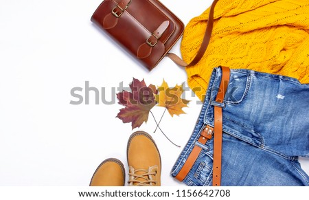Female orange knitted sweater, blue jeans, leather bag, boots and autumn leaves on white background top view flat lay. Fashion Lady Clothes Set Trendy Cozy Knit Jumper Autumn accessories